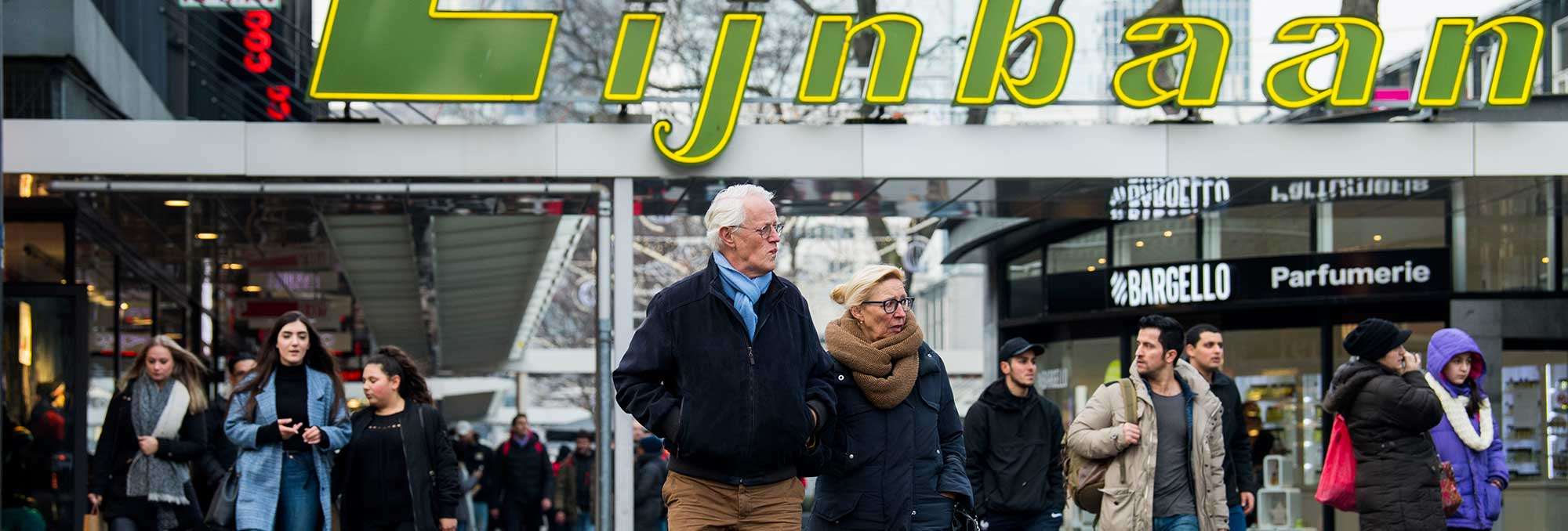 Ouder echtpaar en overige publiek lopend over de Lijnbaan in Rotterdam Centrum, op de pagina Contact van de website van UDSRotterdam