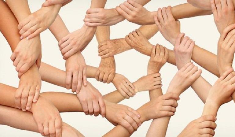 Allemaal armen waarvan de handen elkaars polsen vastpakken, symbool voor samenwerken, bij nieuwsbericht over BIZ
