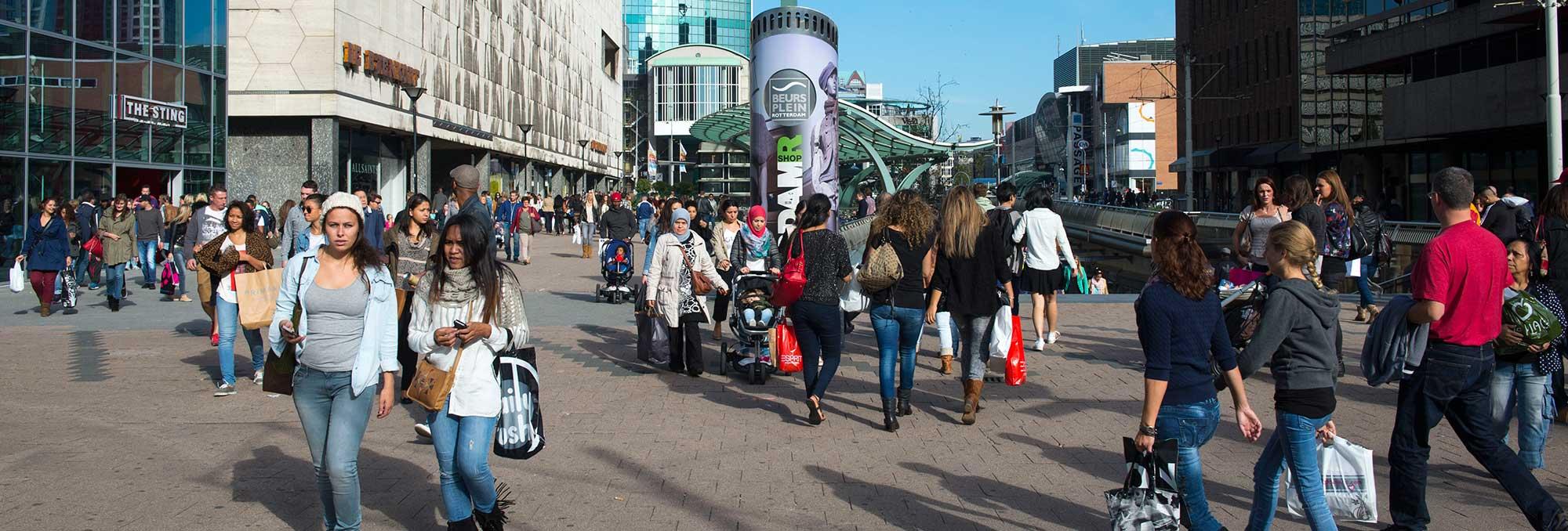 Winkelend publiek op het Beursplein in Rotterdam Centrum, op de pagina Deelgebieden van de website van UDSRotterdam